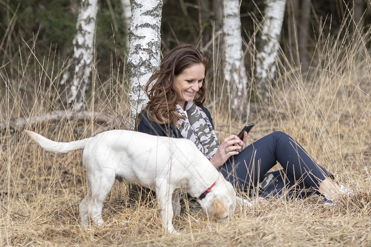 Marion zit tegen een boom met telefoon en hond