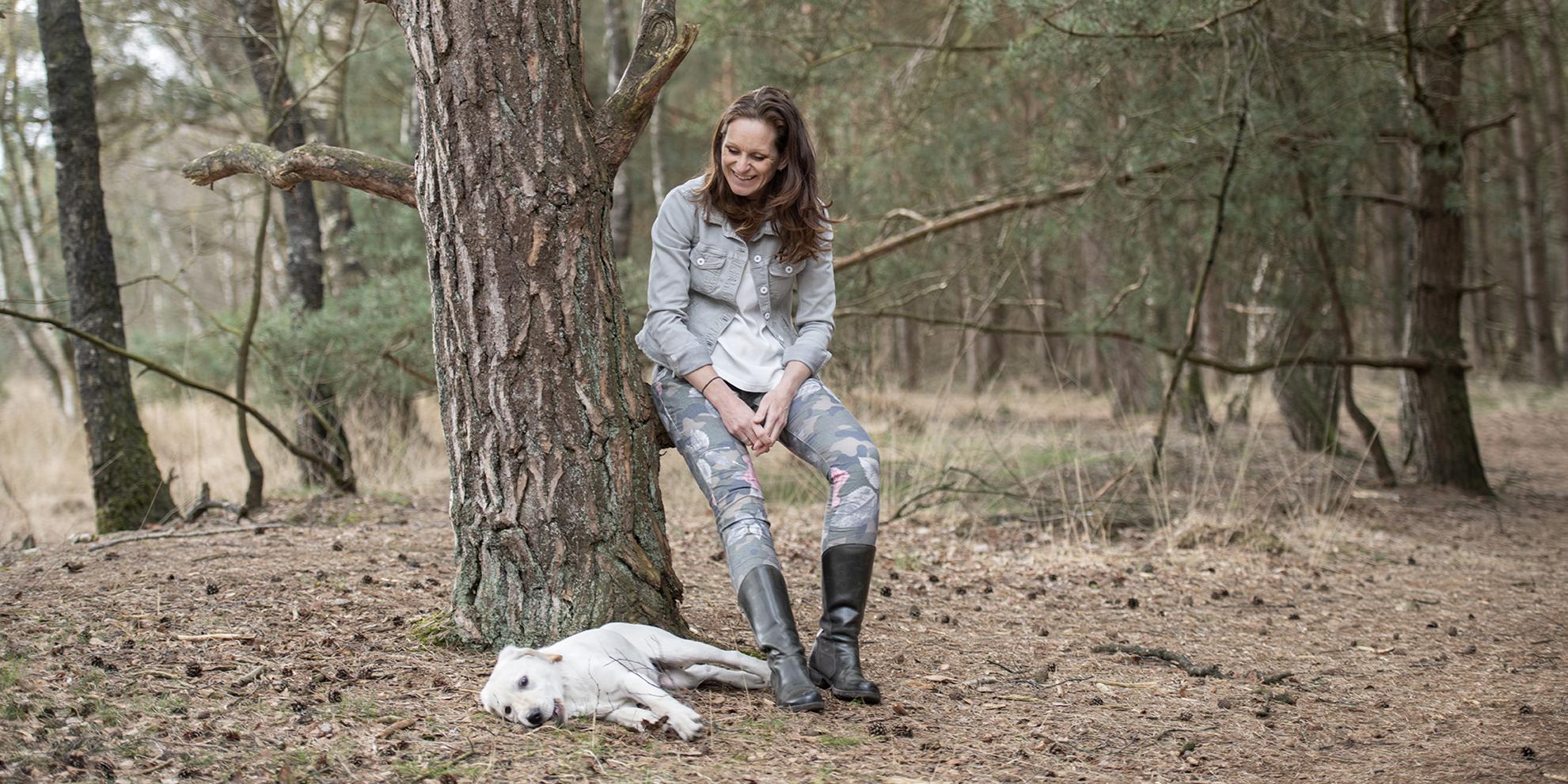 Op een tak in het bos met de hond